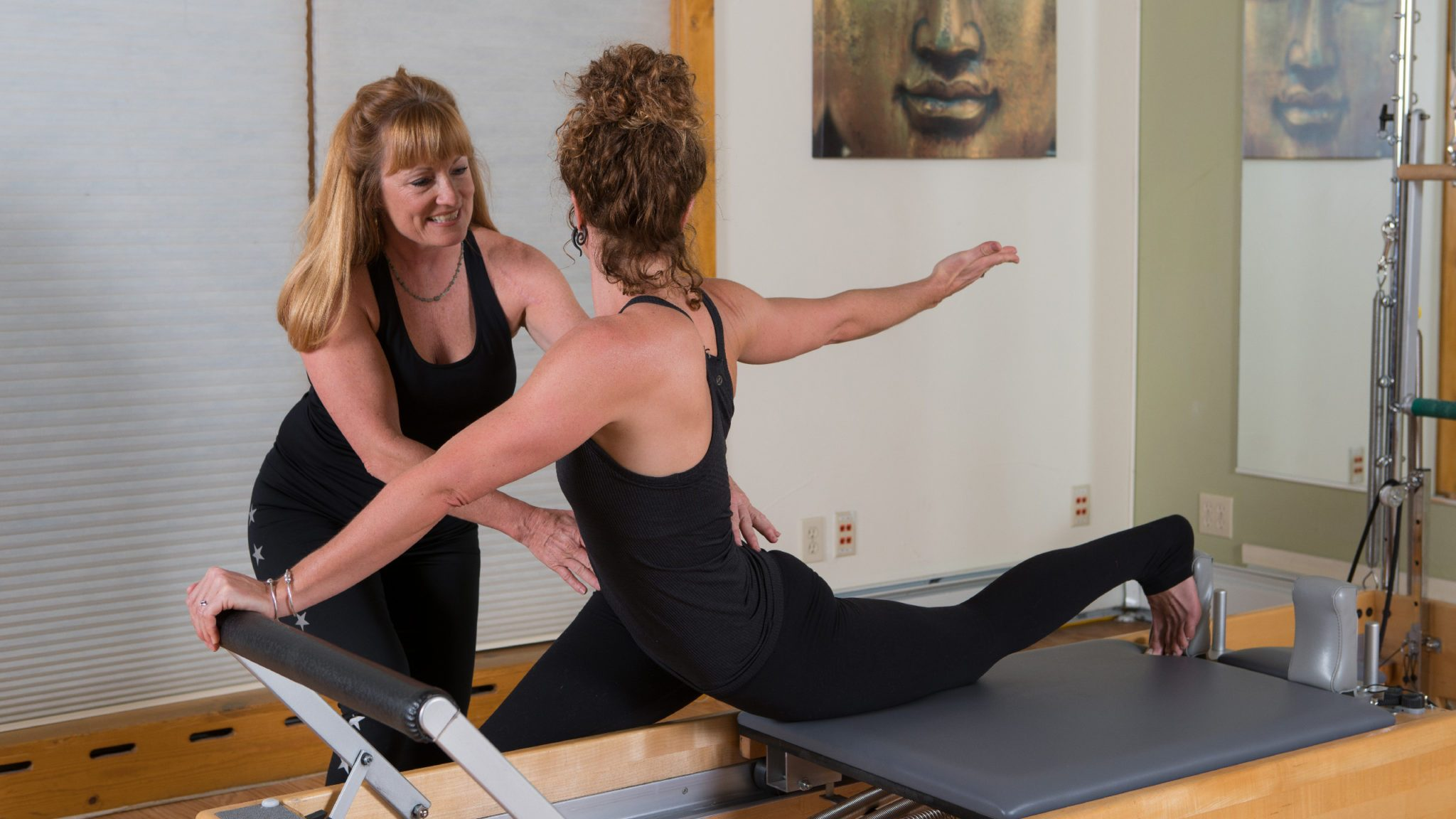 A teacher and student practicing pilates at The Sanctuary