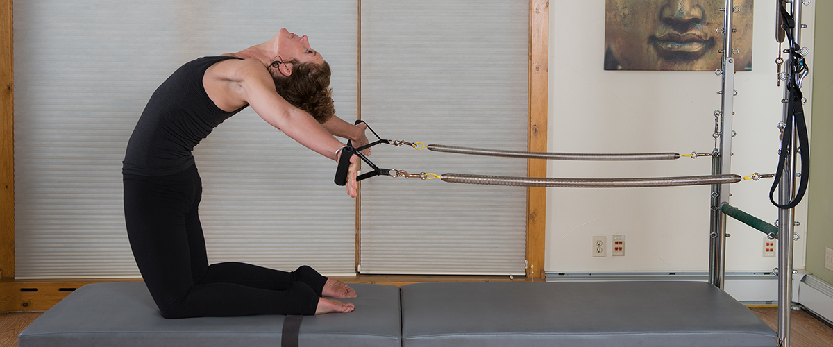 Pilates instructor demonstrating a stretch on the reformer